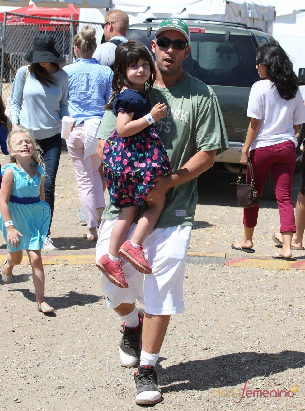 Adam Sandler con su hija en brazos
