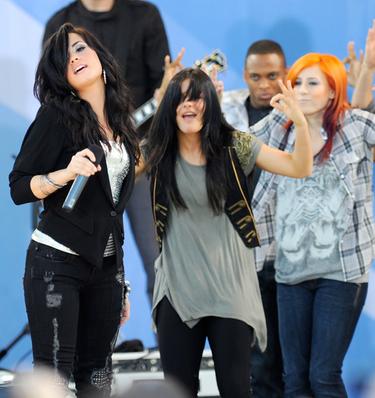 Demi Lovato cantando y Alex Welch, la chica pelirroja, haciendo su papel de bailarina durante la gira con los Jonas Brothers
