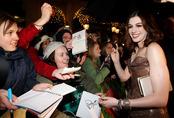 Anne Hathaway firma autógrafos
