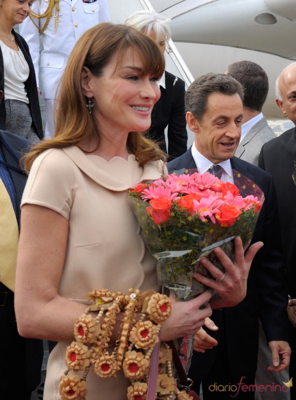 Carla Bruni recibe un ramo de flores a su llegada a la India