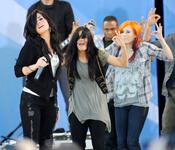 Demi Lovato y Alex Welch (pelirroja) durante una actuación
