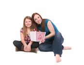 Madre e hija con un paquete de palomitas para ver una película