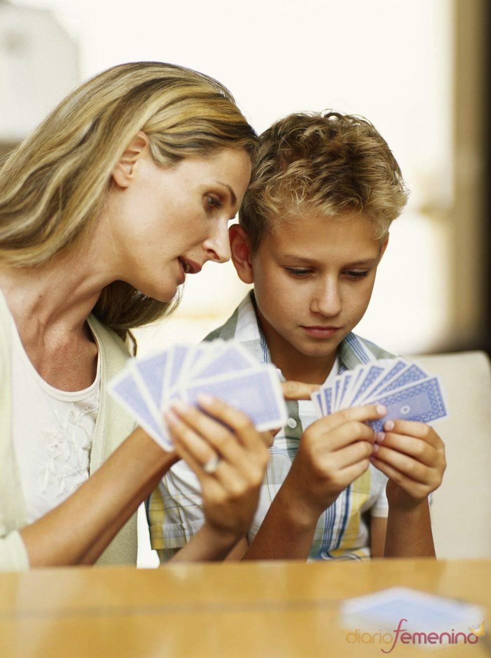 Una madre y su hijo adolescente se divierten jugando a las cartas