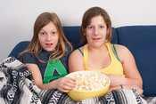 Dos hermanas adolescentes se divierten viendo una película en Navidad