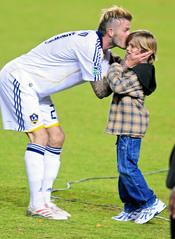 David Beckham dando un beso a su hijo Romeo en un partido