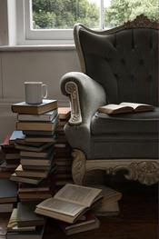 Sillón vintage acompoñado de montaña de libros