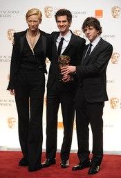 Tilda Swinton, Andrew Garfield y Jesse Eisenberg con el premio de David Fincher al mejor director. Bafta 2011