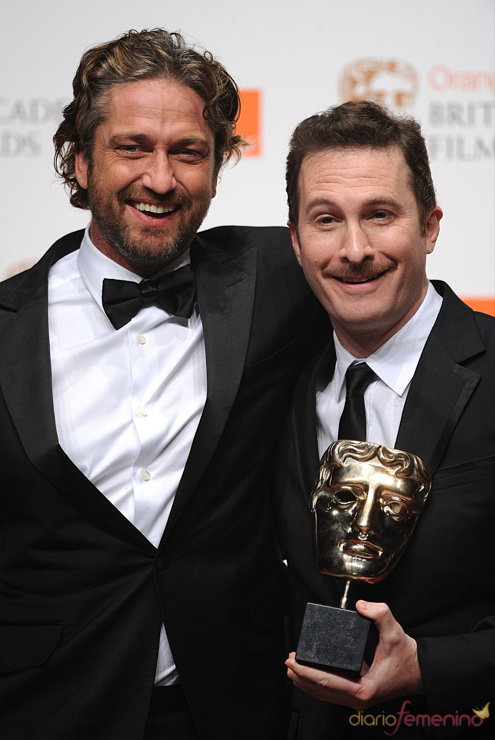 Gerard Butler y Darren Aronofsky en los Bafta 2011 con el premio de Natalie Portman