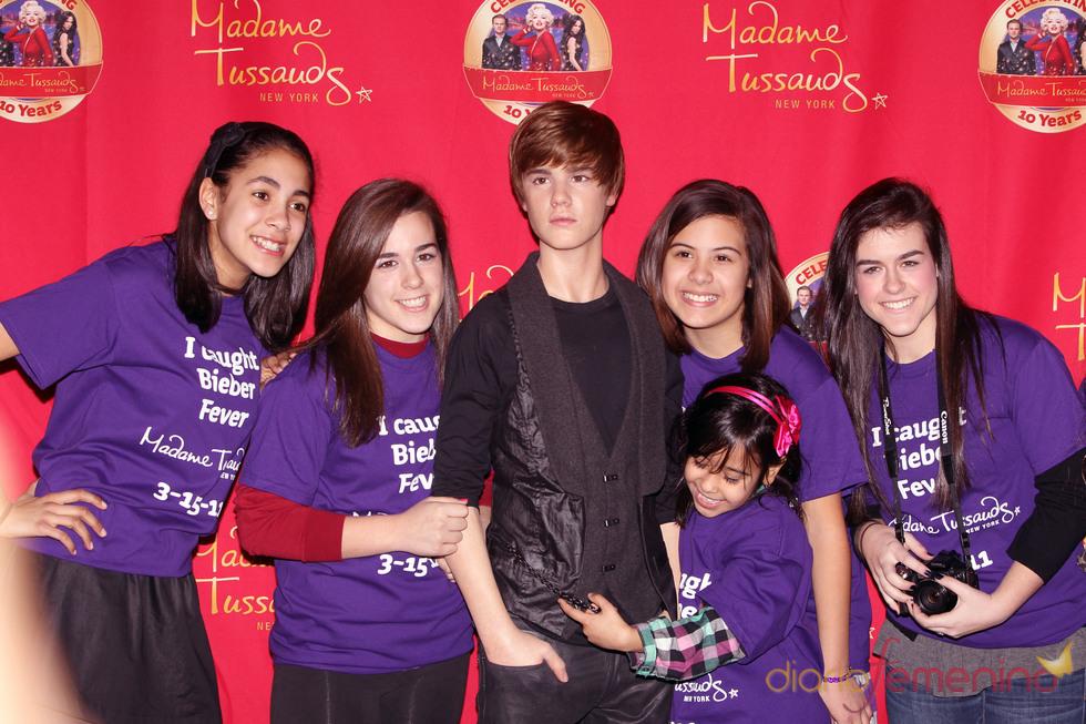 Fans posan alrededor de la figura de cera de Justin Bieber