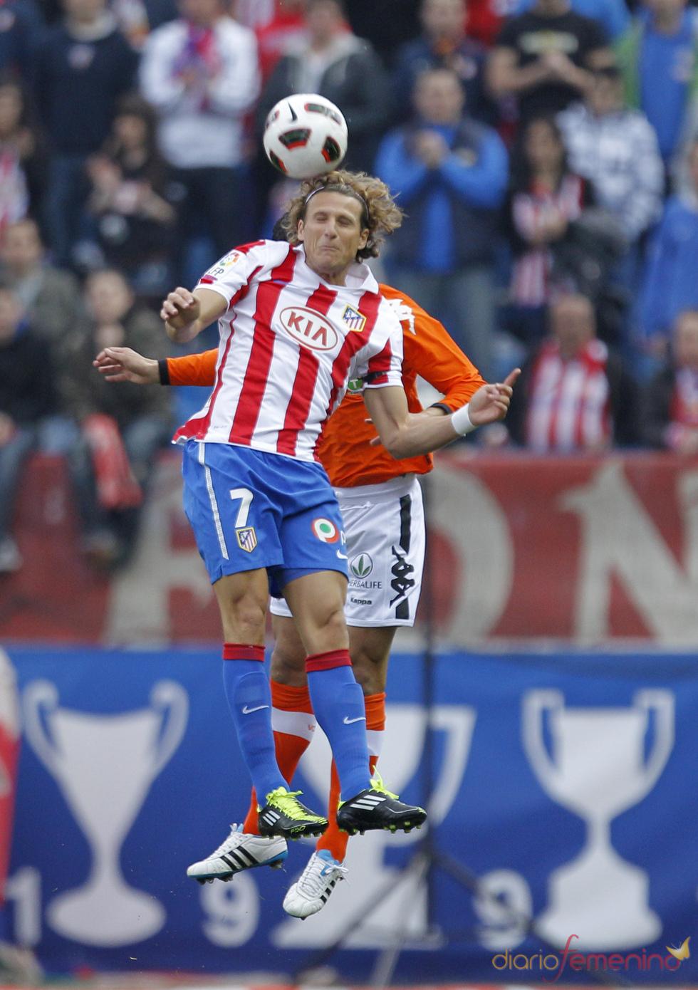 Diego Forlán lucha por el balón en un partido de fútbol