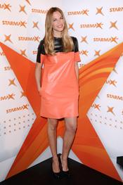 Martina Klein, con un vestido naranja, presenta un evento