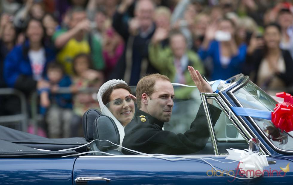 El Príncipe Guillermo y su esposa, Kate Middleton, saludan desde un Aston Martin