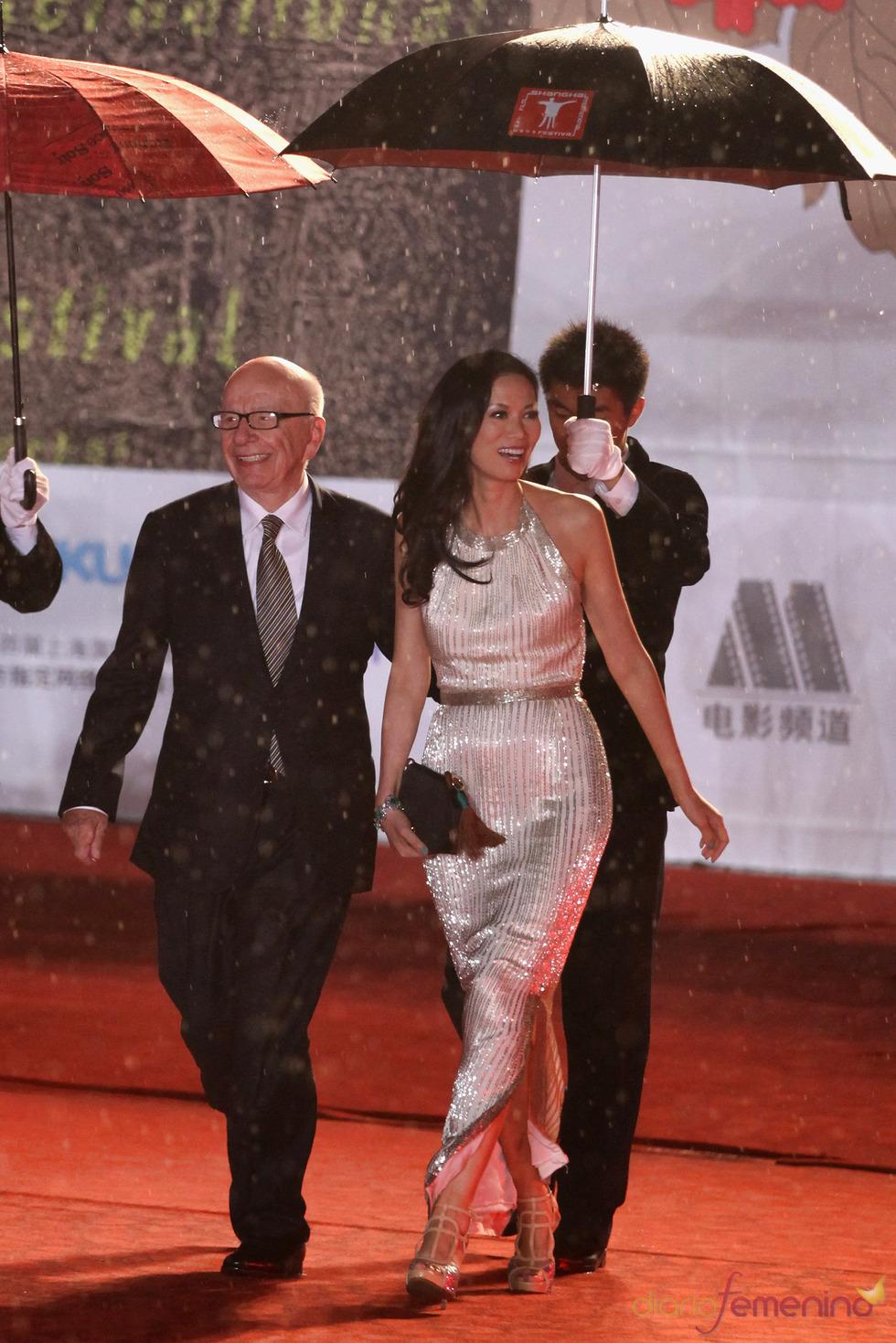 John Woo y Wendi Deng bajo unos paraguas en el Festival de Cine de Shanghái