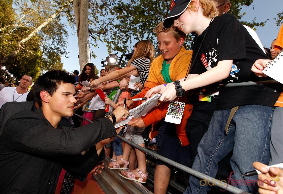Taylor Lautner firma autógrafos