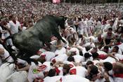 Un toro cae sobre los corredores durante los Sanfermines de 2011