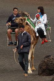 Raúl González y Mamen Sanz paseando sobre un camello