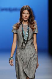 Conjunto de pulseras y collares sobre un sobrío vestido gris de Javier Larrainzar para su colección en Cibeles 2011