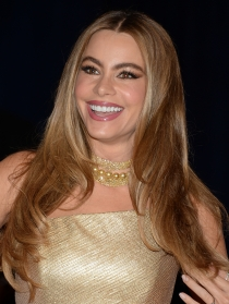 Sofía Vergara, muy sonriente con un vestido dorado
