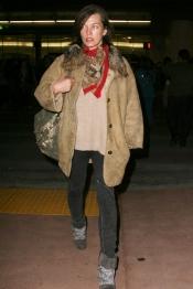 Milla Jovovich con mala cara y al natural al llegar al aeropuerto
